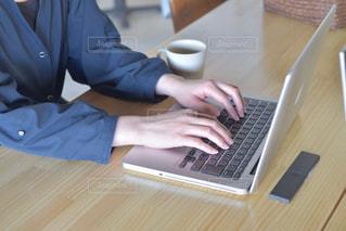 テーブルの上に座っているラップトップコンピュータを使用している人の写真・画像素材[2142866]
