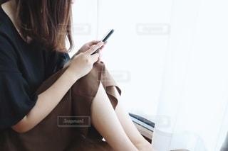 窓際で携帯電話を触る女性の写真・画像素材[2232421]