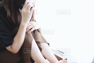 窓際で電話する女性の写真・画像素材[2232425]