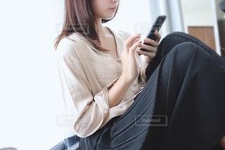 窓際で携帯を触る女性の写真・画像素材[2246758]