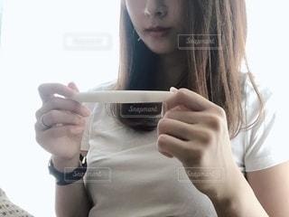 妊娠検査薬を見つめる女性の写真・画像素材[2513825]