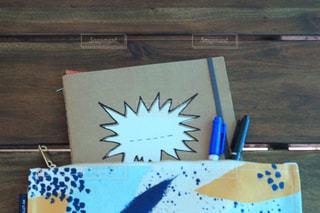 木製テーブル 吹き出し ノート&ペンの写真・画像素材[2080139]