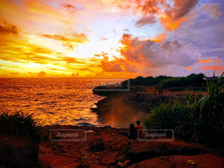 海に沈む夕日をみるカップルの写真・画像素材[1815006]