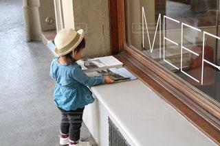 店先に置いてるパンフレットを見る女の子の写真・画像素材[1819344]