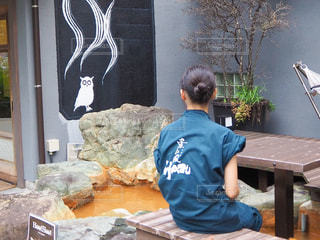 建物の前のベンチに座っている人の写真・画像素材[2461271]