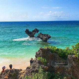 海の近くの岩の上に座っている人々 のグループの写真・画像素材[1843552]