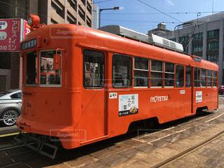 赤い電車は建物の脇に駐車します。の写真・画像素材[1841323]