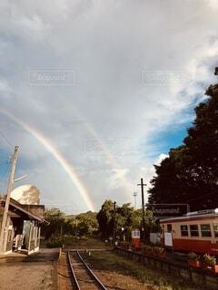 二重の虹が出ている線路上の電車の写真・画像素材[3689585]