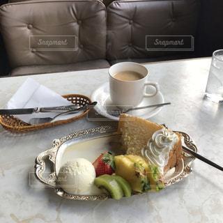 食品やコーヒー テーブルの上のカップのプレートの写真・画像素材[1850521]