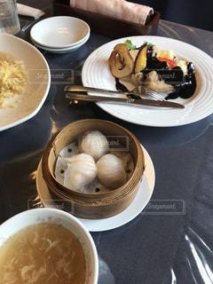 テーブルの上の皿の上に食べ物のボウルの写真・画像素材[1870750]