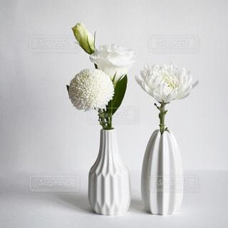 白い花瓶がテーブルの上に座って花でいっぱいの写真・画像素材[1874292]