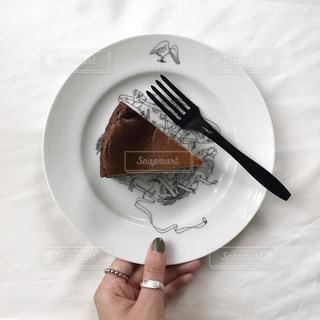 ケーキをフォークで白い板の上に座っています。の写真・画像素材[1879822]