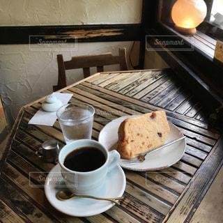 木製のテーブルの上に座っているコーヒー1杯の写真・画像素材[2180713]