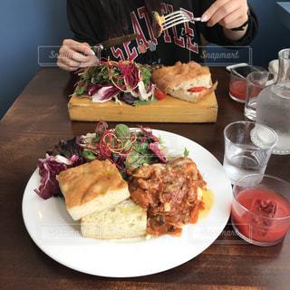 食べ物の皿を持った食卓に座る人の写真・画像素材[2184197]