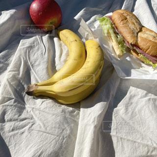 テーブルの上に座っている熟したバナナの束の写真・画像素材[2731363]