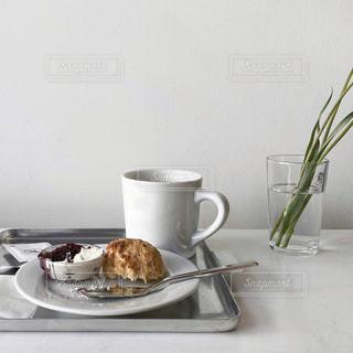食べ物の皿と一杯のコーヒーをテーブルの上に置いての写真・画像素材[3017529]
