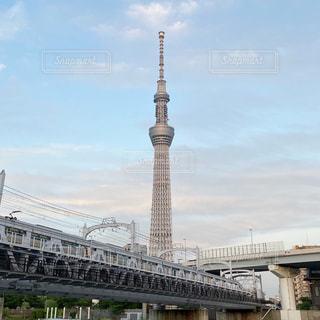 大きな建物に架かる橋を渡る列車の写真・画像素材[3210918]