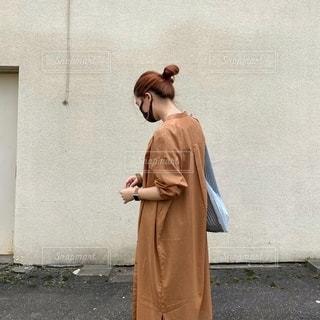 携帯電話で話している建物の前に立っている人の写真・画像素材[3494272]
