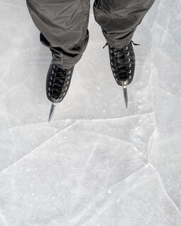 雪に覆われた斜面の下にスノーボードに乗っている男の写真・画像素材[4062775]