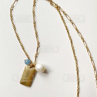 金属の鎖に掛かっているネックレスの写真・画像素材[4156516]