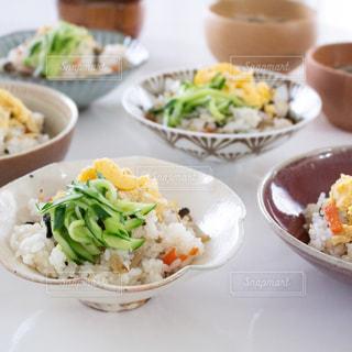 テーブルの上の皿の上の食べ物のボウルの写真・画像素材[2703567]