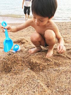 砂浜に座っている小さな子供の写真・画像素材[1879476]
