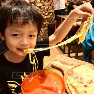 食べ物を食べながらテーブルに座っている小さな男の子の写真・画像素材[2345556]