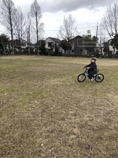 芝生のフィールドで自転車に乗る人の写真・画像素材[1873903]