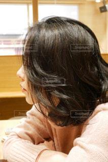 窓の近くに座っている女性の写真・画像素材[2849989]