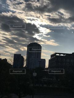 落ちる夕陽を追う雲の群れの写真・画像素材[309311]