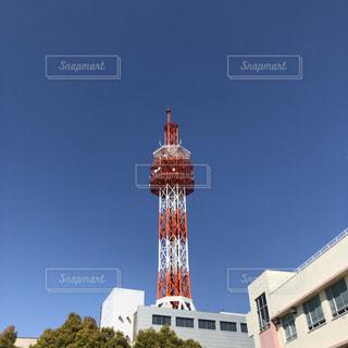 建物の側に時計と大きな背の高い塔の写真・画像素材[1921912]