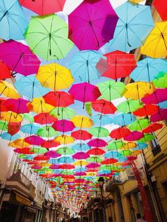 そこからぶら下がっている色の異なる傘の束の写真・画像素材[2345232]