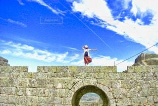レンガの壁の前に立っている人の写真・画像素材[2361006]