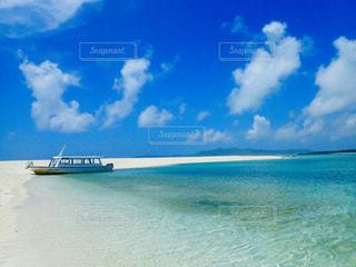 水の体の隣に座っている青と白のボートの写真・画像素材[2390048]