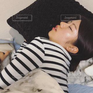 ベッドの上で横になっている人の写真・画像素材[1944426]