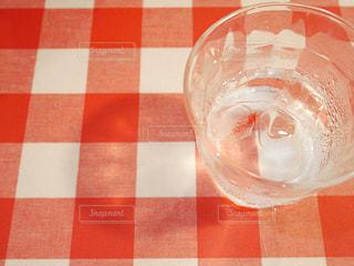 赤チェックのクロスとグラスの水の写真・画像素材[2190574]
