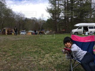 芝生に座っている小さな男の子の写真・画像素材[865057]