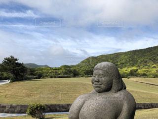 野原の真ん中の岩の上に座っている人の写真・画像素材[2880667]
