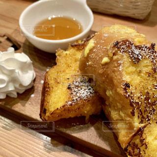 近くに木製のテーブルの上のパンの部分のアップの写真・画像素材[1918750]