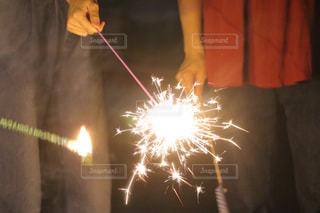 火のついたキャンドルでバースデーケーキの前に立っている男の写真・画像素材[2511539]