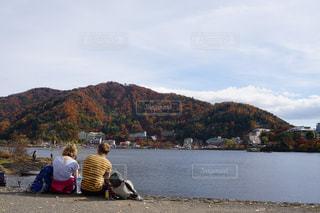 水の体の横に座っている人々 のグループの写真・画像素材[814408]