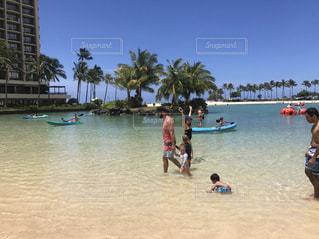 水の体の近くのビーチの人々 のグループの写真・画像素材[1914870]