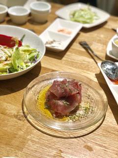 木製のテーブルの上に座っている食べ物の皿の写真・画像素材[2271053]