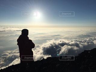 雲海から昇るご来光を眺める俺の写真・画像素材[1908818]