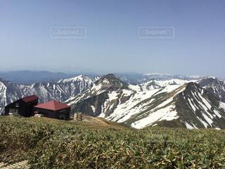 山小屋と雪に覆われた山の写真・画像素材[1910666]