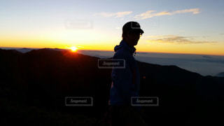 日の出の前に立っている男の写真・画像素材[1910674]