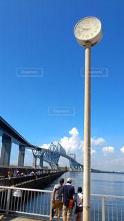 水の体の横に桟橋の前に立っている男の写真・画像素材[976759]