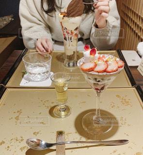 ワイングラスを持ってテーブルに座っている人々のグループの写真・画像素材[2827131]