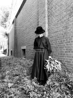 レンガ造りの建物の前に立っている男の写真・画像素材[2827141]