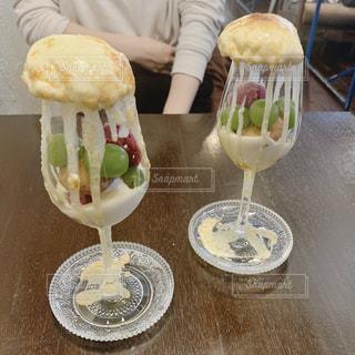 食べ物の皿を持ってテーブルに座っている人の写真・画像素材[2827143]